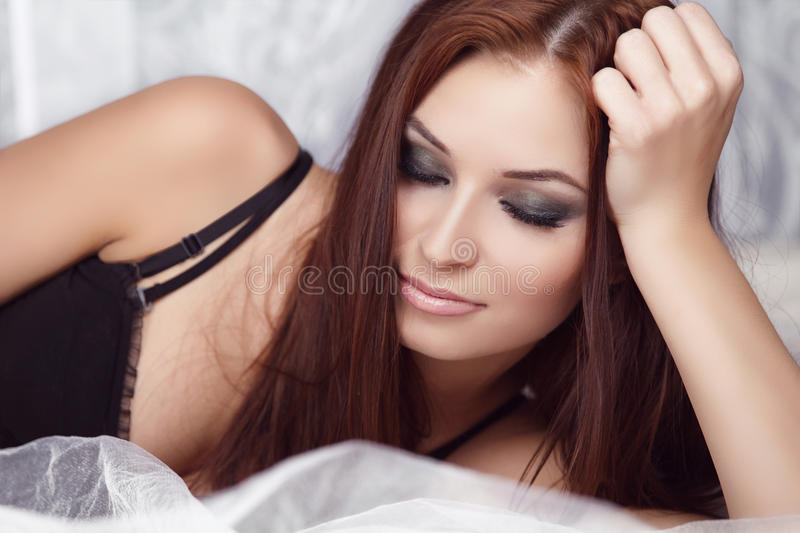 Eyes Makeup. Fashion portrait of beautiful brunette woman resting on bed stock photo
