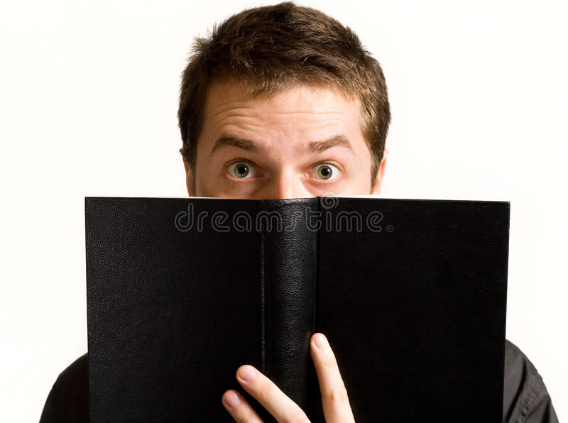 Eyes of surprised man above book royalty free stock photography
