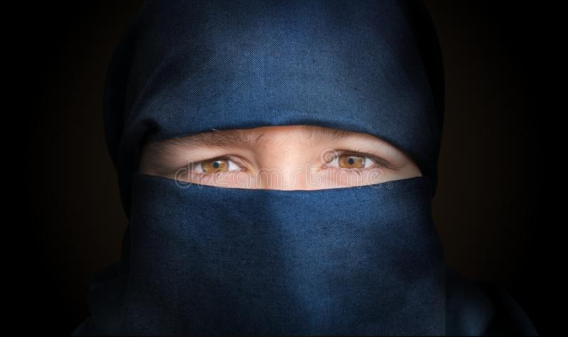 Eyes of young woman veiled with blue niqab scarf. Low key photo.  royalty free stock photography