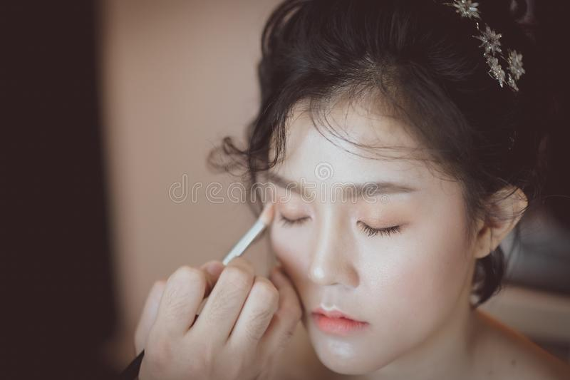 Eyeshadow and beautiful Asian model. Makeup artist applying pink eyeshadow to beautiful Asian model, white, girl, face, skin, beauty, woman, fashion, background royalty free stock photography