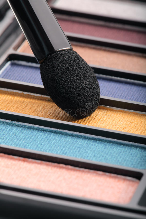 Eyeshadow. Close up of coloured eyeshadows and applicator royalty free stock images