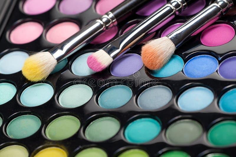 Eyeshadow kit with three makeup brushes royalty free stock photos