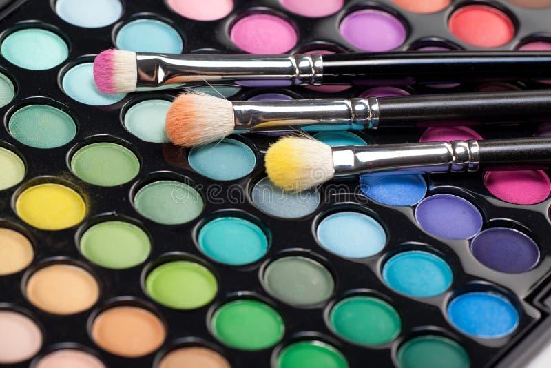 Eyeshadow kit with three makeup brushes stock image