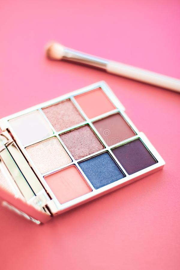 Eyeshadow palette and make-up brush on coral background, eye shadows cosmetics product for luxury beauty brand promotion and royalty free stock images