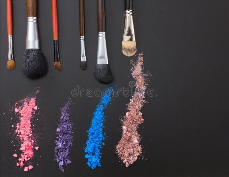 Eyeshadows and make up brushes on black background. Summer fashion style. Copy space. Eyeshadows and make up brushes on black background. Summer fashion style royalty free stock images