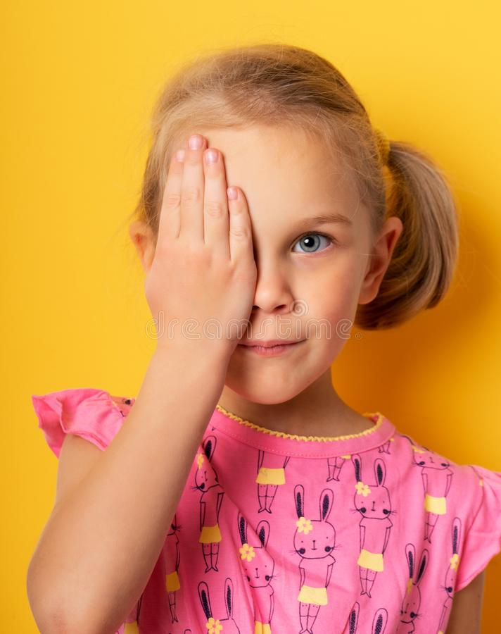 Eyesight check. girl covering one eye with hand. ophthalmology concept. Eyesight check. girl covering one eye with hand. eyesight check and health examinations stock images
