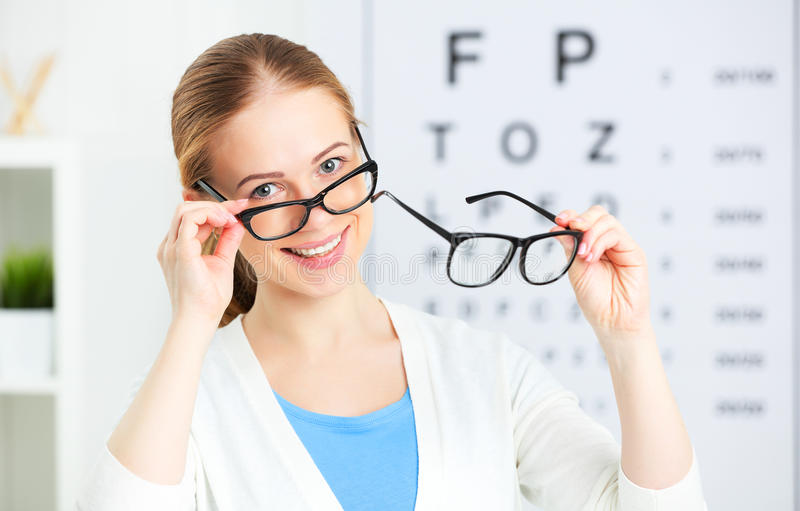 Eyesight check. woman choose glasses at doctor ophthalmologist o royalty free stock photo