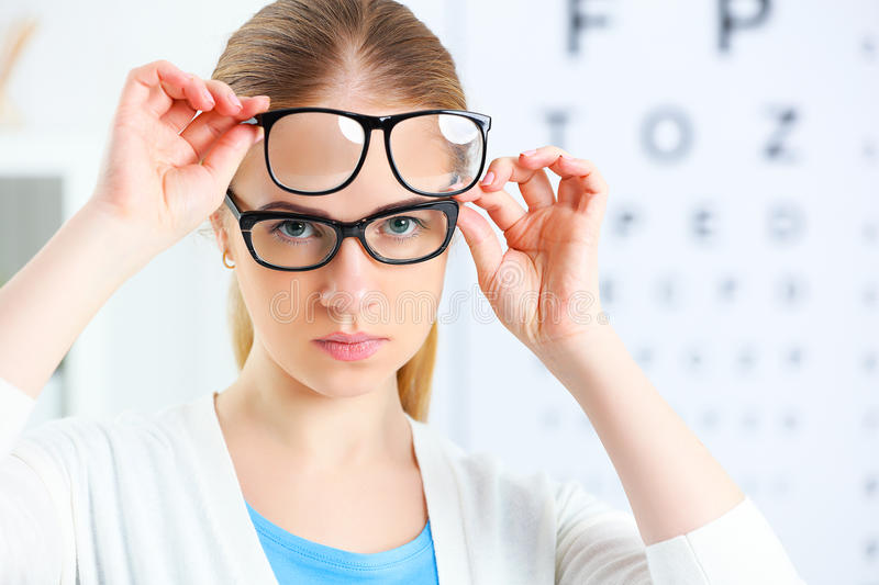 Eyesight check. woman choose glasses at doctor ophthalmologist o stock photography