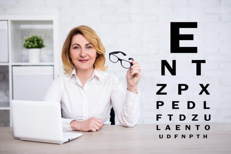 Eyevision provdiagram och kvinna för mogen affär som använder bärbara datorn och rymmer glasögon i modernt kontor arkivbild