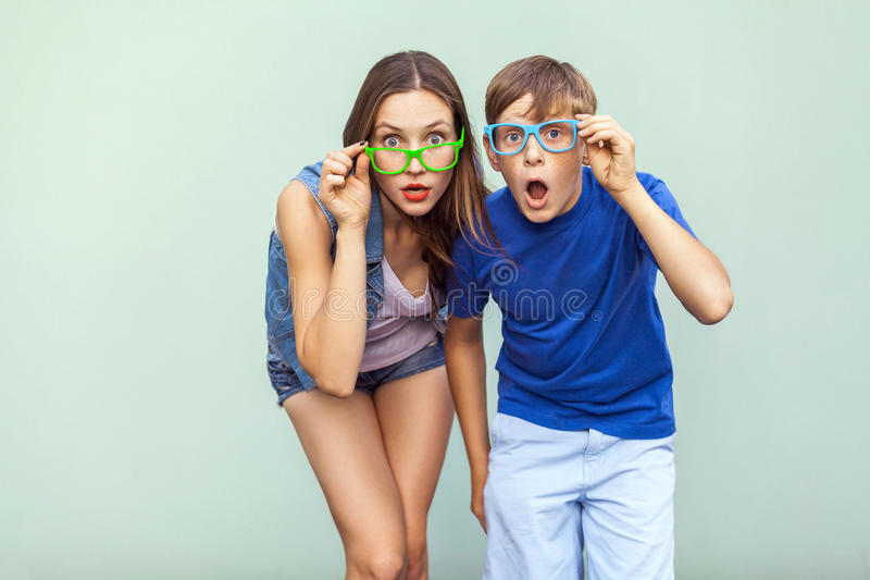 Eyewear concept. WOW faces. Young sister and brother with freckles on their faces, wearing trendy glasses, posing over light green stock photos