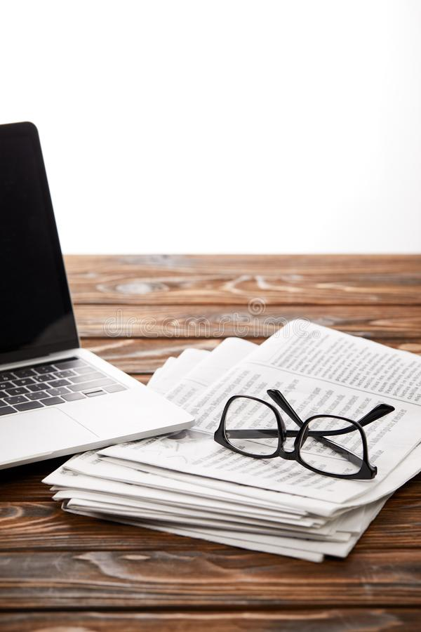eyewear op stapel van kranten en laptop op houten lijst, aangaande wit royalty-vrije stock foto