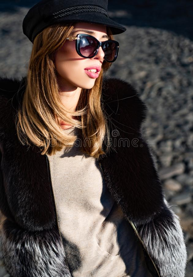 Eyewear trend. Pretty woman in hat and sunglasses and furry vest urban background. Fall fashion accessory. Enjoy fall. Season. Woman enjoy sunny day outdoors stock photo