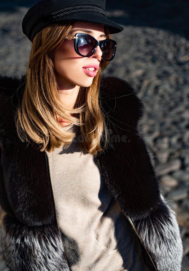 Eyeweartendens Mooie vrouw op hoed en zonnebril en bontvest stedelijke achtergrond De toebehoren van de dalingsmanier Geniet van  stock foto