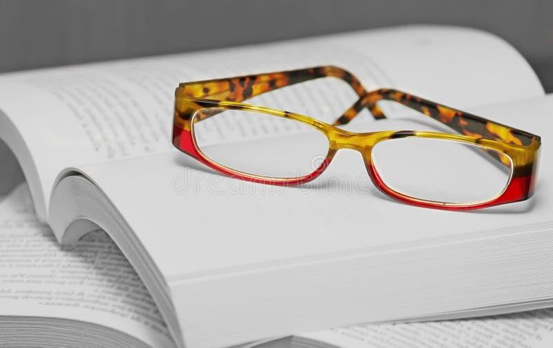 Eyglasses en una pila de libros imagen de archivo libre de regalías