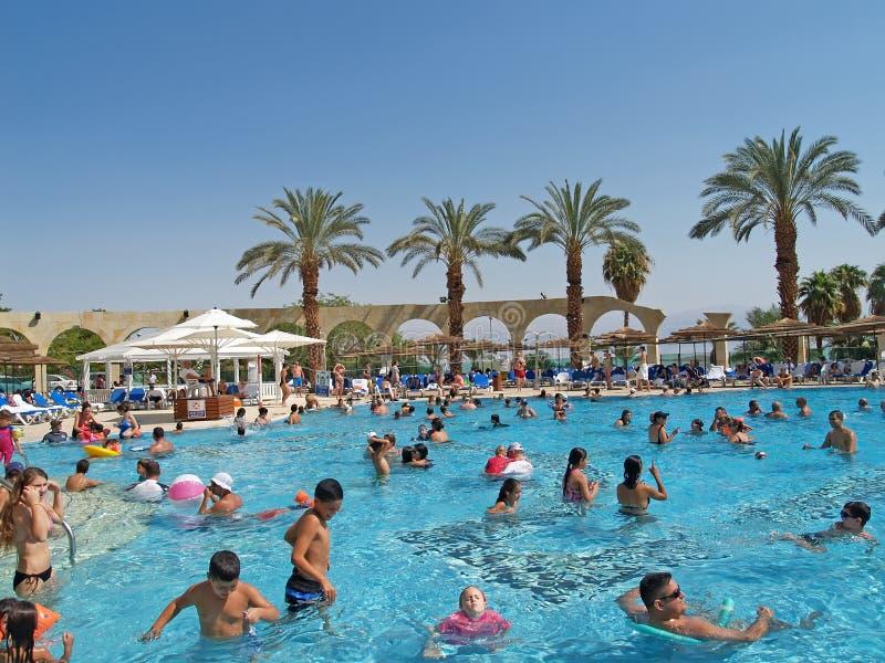 EYN-BOKEK ISRAEL Folket simmar i pölen med sötvatten på banken av det döda havet royaltyfri bild