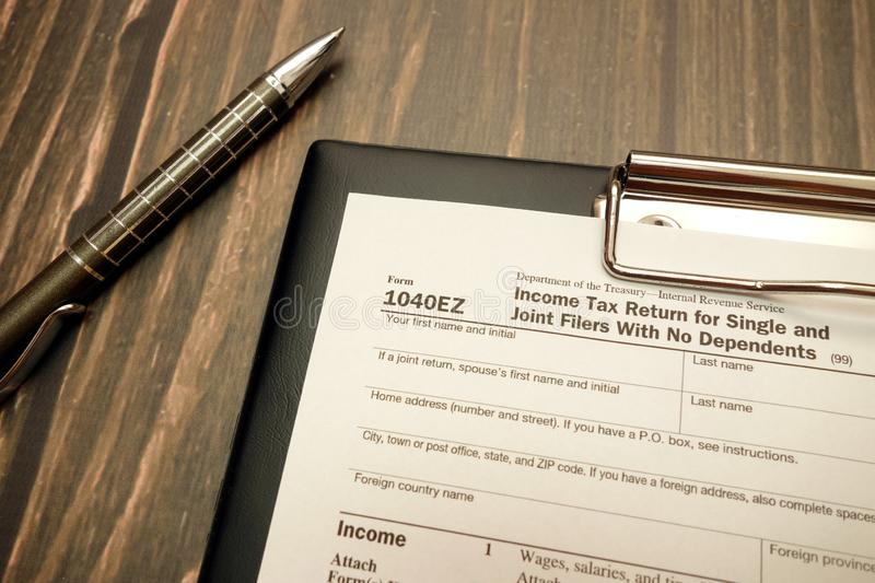 1040EZ form, income tax return for single and joint filers and pen. On wooden desk royalty free stock photography