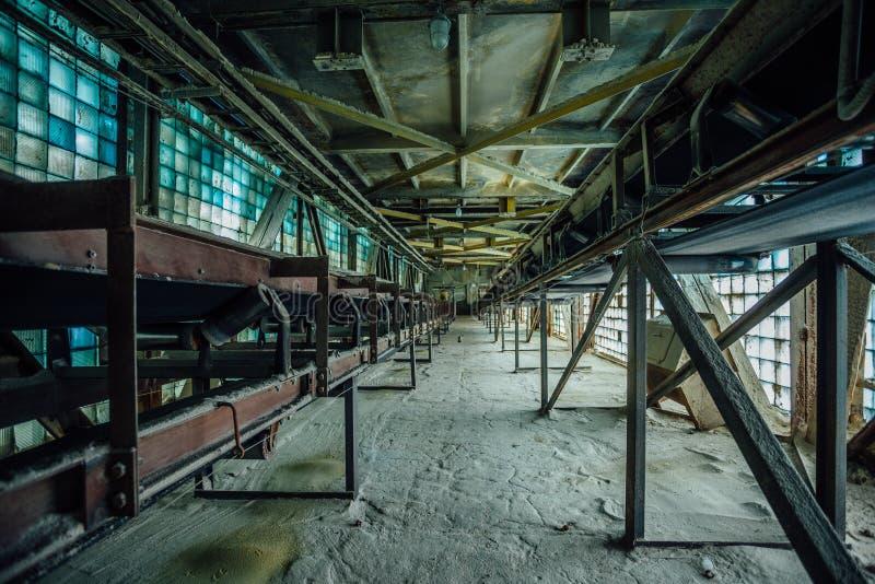 Fábrica abandonada Correia transportadora empoeirada velha no corredor velho do tijolo de vidro fotos de stock royalty free