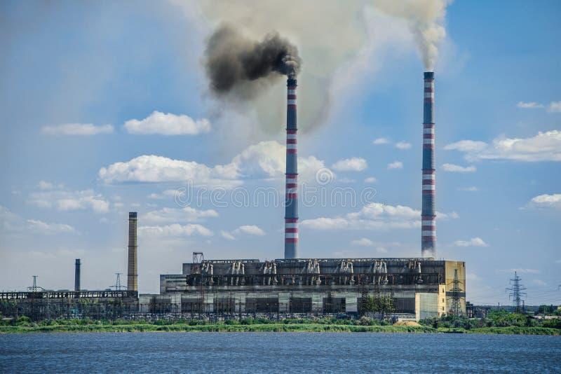 Fábrica al lado del río con la contaminación atmosférica fotografía de archivo