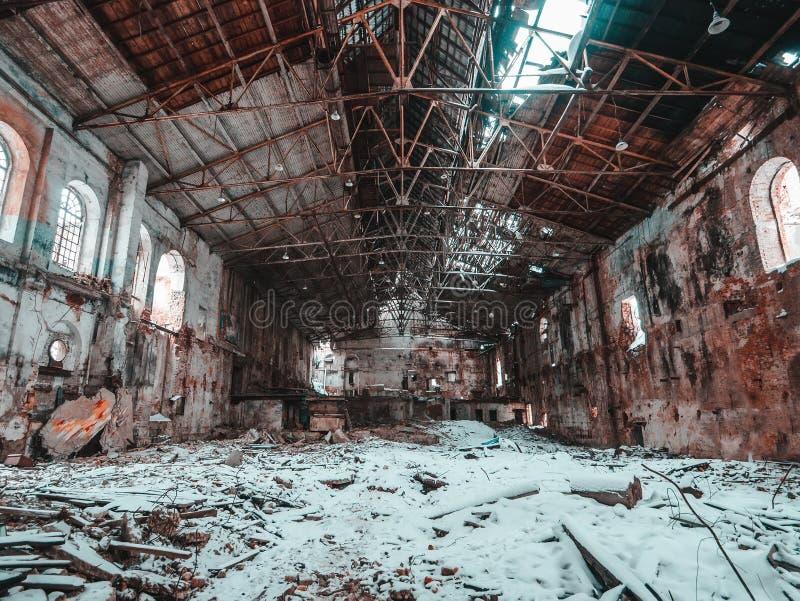 Fábrica arruinada o pasillo abandonado del almacén con el tejado quebrado y nieve en el piso, concepto nuclear del invierno foto de archivo
