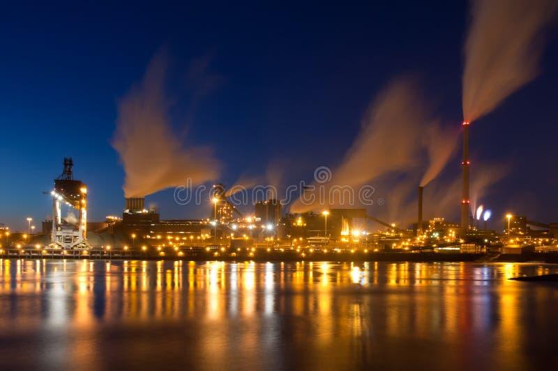 Fábrica de acero holandesa con las chimeneas en la noche fotografía de archivo