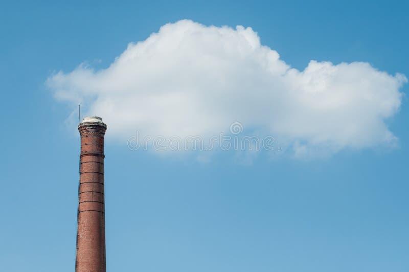 fábrica de la chimenea del ladrillo en el cl blanco del fondo del cielo azul imagen de archivo