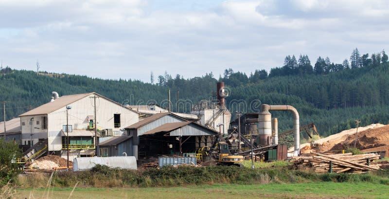 Fábrica de processamento da madeira serrada com uma máquina escavadora fotos de stock royalty free