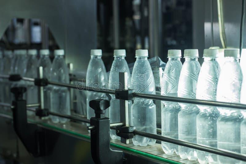 Fábrica del agua - línea de embotellamiento de agua para procesar y embotellar el agua de manatial pura en las pequeñas botellas foto de archivo libre de regalías