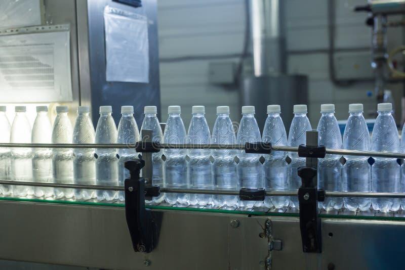 Fábrica del agua - línea de embotellamiento de agua para procesar y embotellar el agua de manatial pura en las pequeñas botellas imagen de archivo