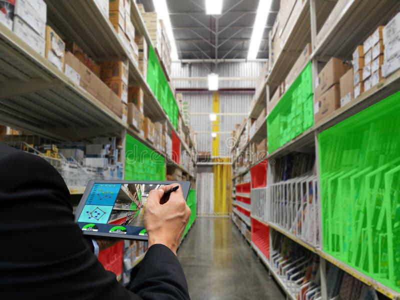 Fábrica do armazenamento dos produtos da verificação da tecnologia da tabuleta da terra arrendada da mão do homem de negócios fotos de stock royalty free