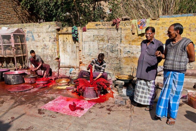 Fábrica exterior e trabalhadores de matéria têxtil da vila que pintam a roupa imagens de stock
