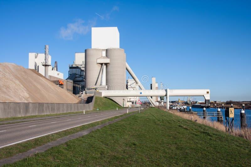 Cemente la fábrica cerca de un canal en los Países Bajos fotografía de archivo libre de regalías