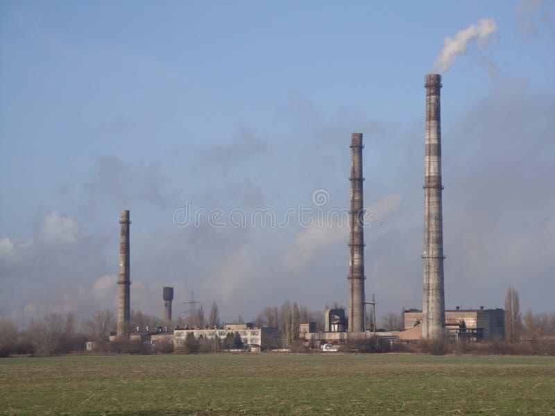 Fábrica industrial con tres tubos que fuman en clubs de la niebla con humo Cielo azul fotografía de archivo libre de regalías