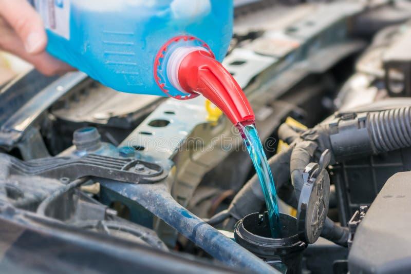 Füllen des Wasserbehälters mit Frostschutzmittel im Motorraum eines Autos lizenzfreies stockbild