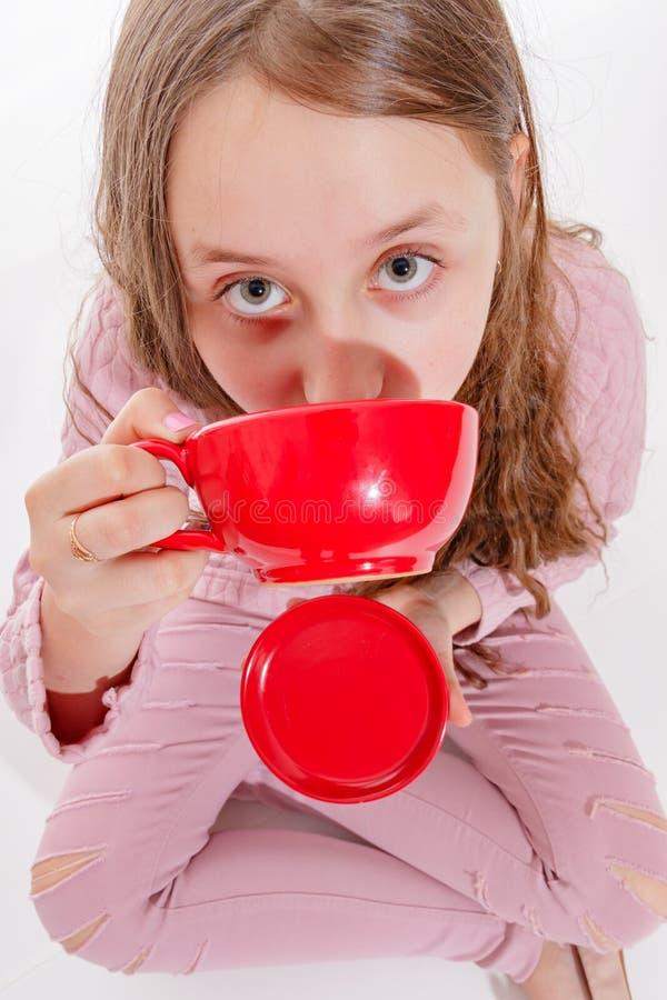 Fünf O-` Uhr Tee Ein lächelndes Mädchen trinkt ein heißes Getränk beim Sitzen auf dem Boden lizenzfreie stockfotos