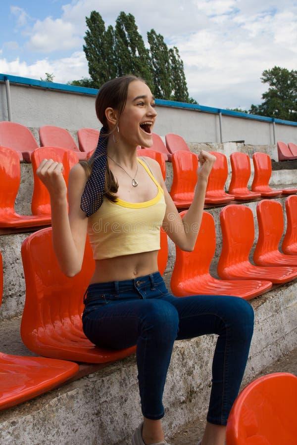 Fã adolescente do suporte da menina no jogo do estádio imagens de stock