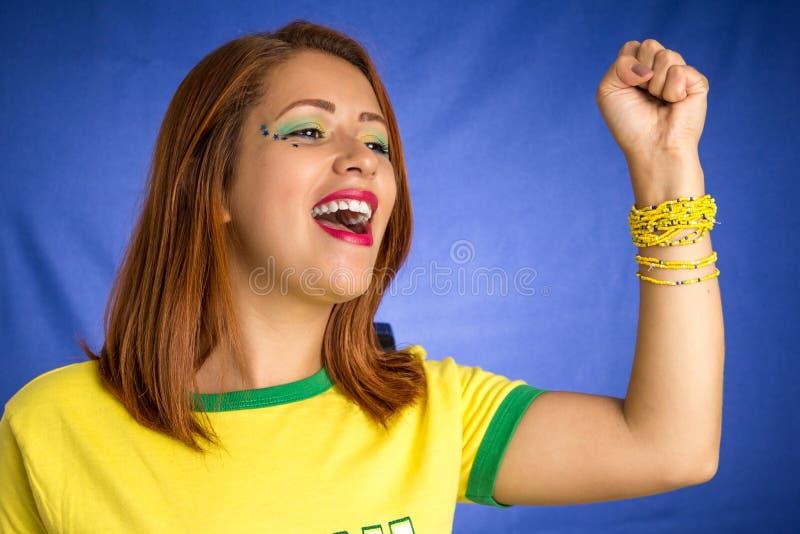 Fã brasileiro da mulher que comemora no fósforo de futebol no backgr azul imagens de stock
