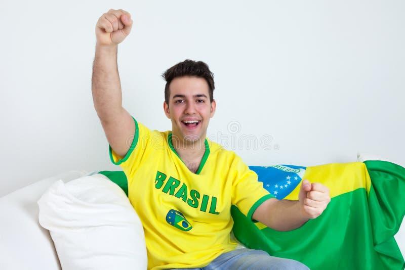 Fã de esportes brasileiro Cheering no sofá foto de stock royalty free