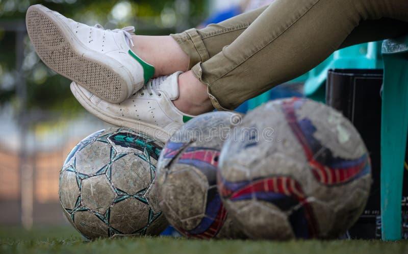 Fã de esportes do espectador do jogo de futebol do futebol que descansa no banco e em bolas gastadas do futebol no campo, fundo o fotografia de stock