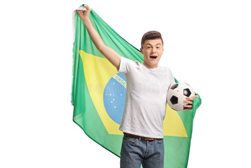 Fã de futebol adolescente alegre que guarda um futebol e um fla brasileiro fotografia de stock