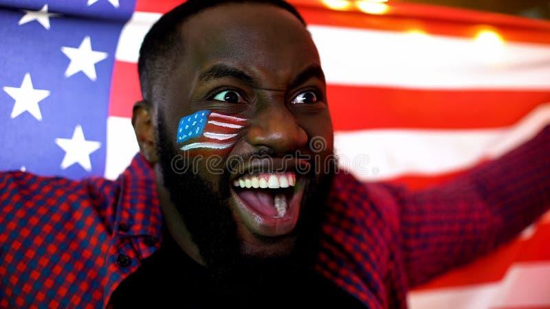 Fã de futebol afro-americano emocional que guarda a bandeira nacional, cheering para a equipe imagem de stock