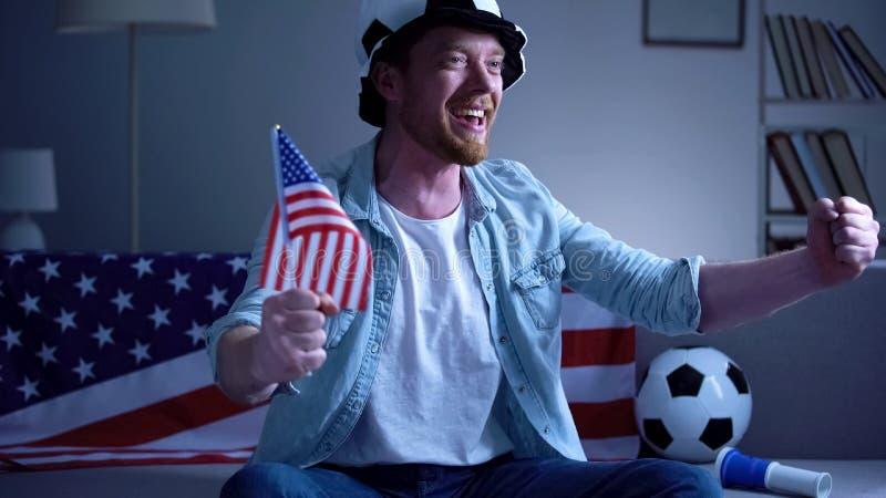 Fã de futebol americano que guarda a bandeira dos EUA, fósforo de futebol de observação na tevê em casa imagens de stock royalty free