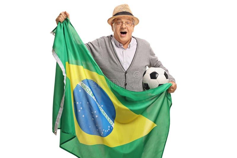 Fã de futebol idoso entusiasmado que guarda um futebol e um fl brasileiro imagens de stock