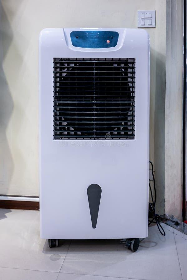 Fã e humidificador eletrônicos da torre da sala na parede branca foto de stock