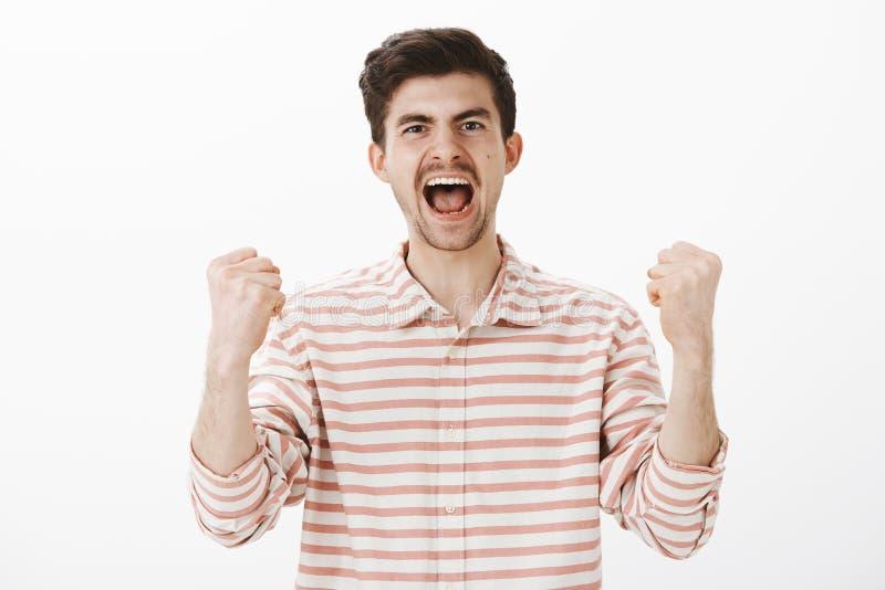 Fã verdadeiro alegre para sua equipe favorita Disparado do colega de trabalho masculino considerável de triunfo, gritando da feli imagens de stock royalty free