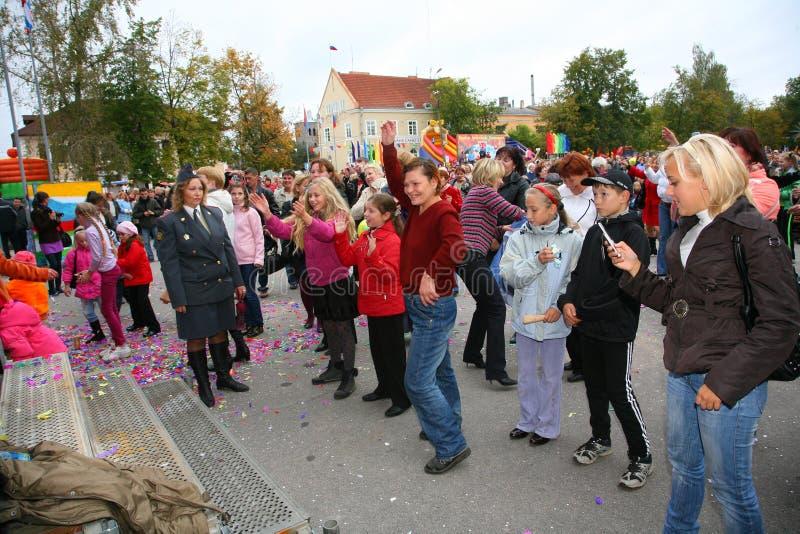 Fãs da estrela, dos adultos e dos ouvintes que populares das crianças um bravo livre do concerto da rua aplaude, exulta e dança foto de stock