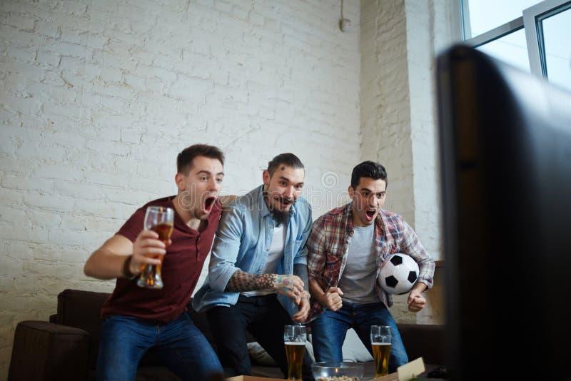 Fãs de esportes que comemoram o objetivo fotografia de stock