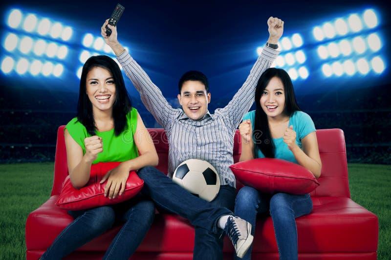 Fãs de futebol ectáticos que olham a tevê fotografia de stock