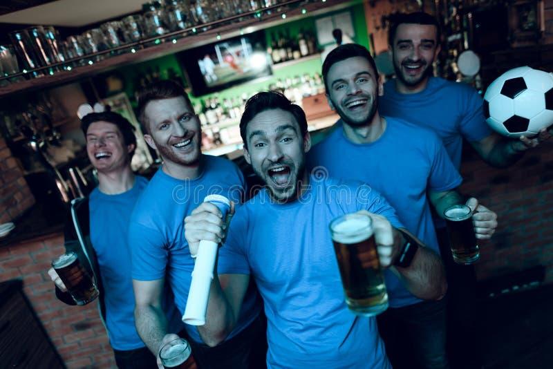 Fãs de futebol que comemoram o objetivo e que cheering na frente da cerveja bebendo da tevê na barra de esportes imagens de stock