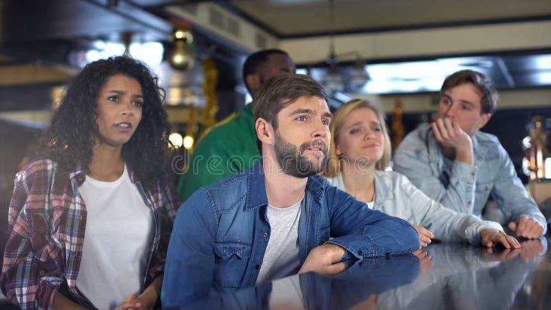 Fãs portugueses com virada da bandeira nacional sobre a perda, esportes de observação na barra imagens de stock royalty free