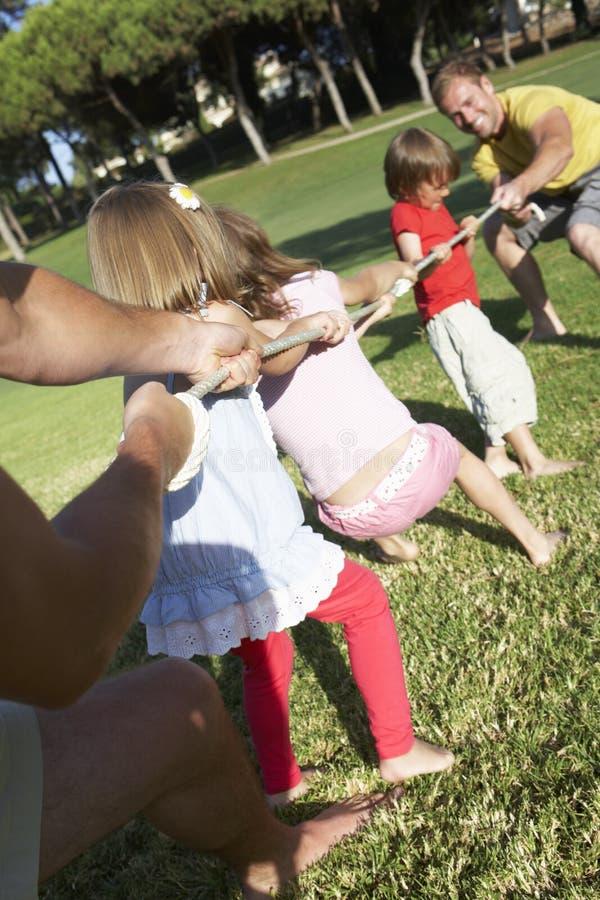 Fäder och barn som spelar dragkampen arkivfoto